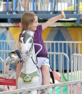 Ava Denniston waves to her family as she enjoys a ride at the fair.