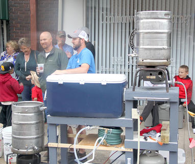 Chris Cracraft, with the hat on, gave a demonstration on how to brew beer. Enjoying the fruits of that labor is friend Chris Bowlin.
