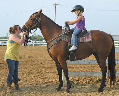 Chelsey Choate gives Quick a good luck kiss before her performance during the Harrison County Fair's fun horse show on July 7. Riding Quick is Danielle Choate.