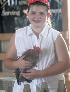 Ten-year-old Josie Tucker won two blue ribbons with the chicken she is holding.