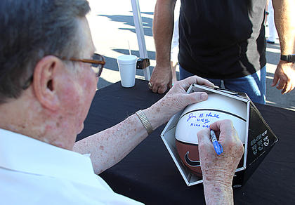 Coach Hall signs a basketball, which was just one of a number of UK memorabilia that Hall and former Wildcats autographed Tuesday evening during the reveal ceremony for Hall's mural.