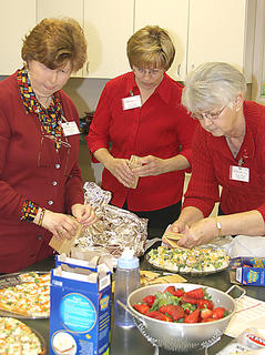 Go Red committee members prepared snacks for Monday&#039;s reception.  They are, from left, Rachel Mastin, Diane Burton, and Wanda Marsh.