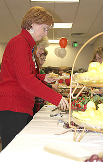 Martha Sullivan grabs a healthy snack at the Go Red Reception held Monday at the Cynthiana Christian Church. The reception is held annually to bring awareness to heart disease.