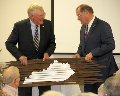 "Mike Denham presents Tom McKee with a ""tobacco stick"" map of Kentucky."