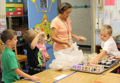 Angie Mattox, Kindergarten teacher at Eastside Elementary helps her students with their breakfast choices.