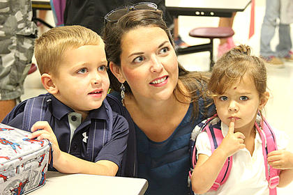 Austin Wright is ready for his first day of school. His sister, Lucy, is not so ready to let him go. Also pictured is their mom, Samantha Wright.