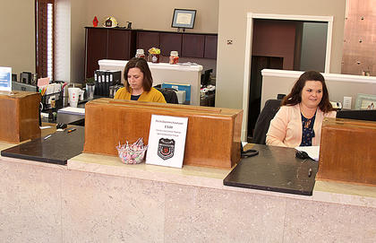 Greeting customers paying their bills are deputy clerks Elizabeth Faulkner and Leslie Mullett.