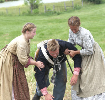 Women help a wounded soldier off the battlefield.
