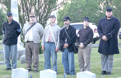 Union and Confederate soldiers pay their respects to fallen soldiers.