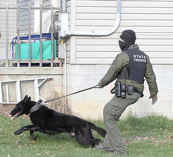 Kentucky State Police Tpr. Jack Gabriel and his K9 check a house on Pearl Street where a suspected trafficker was living.