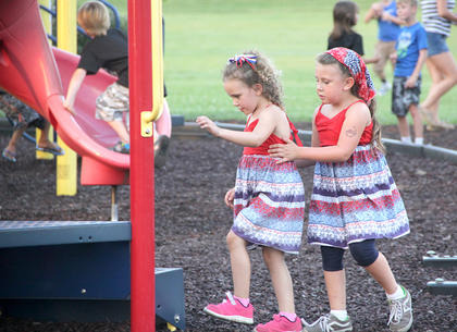Two pretty young ladies were dressed alike and enjoyed the playground on Saturday.