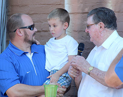Coach Hall encourages his great-grandson to sing The National Anthem.