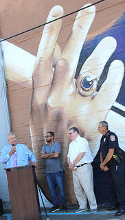 Harrison County Judge-Executive Alex Barnett says a few words as muralist Sergio Odeith, Coach Hall and Chief of Police Ray Johnson look on.
