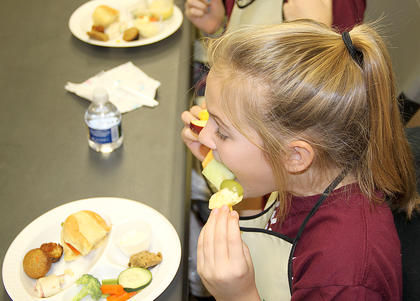 Finally!!  The food has been carefully prepared and it's time to taste! Audrey Dawson digs into a fruit ka-bob.