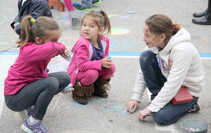 Several activities were set up for children, including chalk drawing, a connect-four game, and a ball pit. Some children also took advantage of trees in the courthouse lawn to work on their climbing skills.