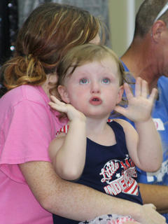 Eliza Choate plays peek-a-boo while waiting for the results of the baby show. She is the daughter of A.J. Choate and Haley Stratton.